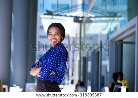 Portrait of a smiling african business woman with arms crossed - stock photo
