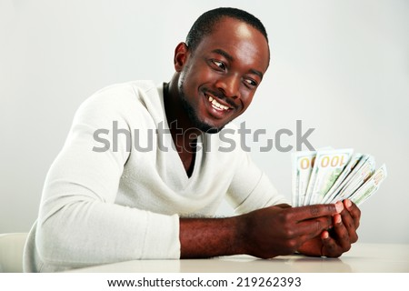 Portrait of a smiling african man holding US dollars - stock photo