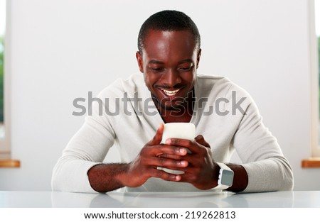 Portrait of a smiling african man using smartphone - stock photo