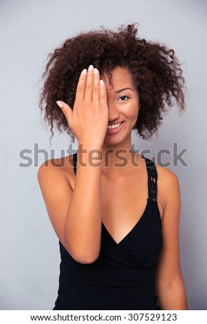 Portrait of a smiling afro american woman covering her eye and looking at camera over gray background - stock photo