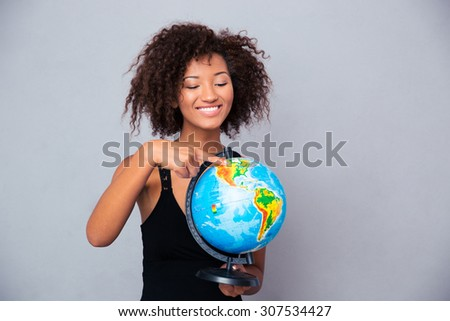 Portrait of a smiling afro american woman holding globe over gray background - stock photo