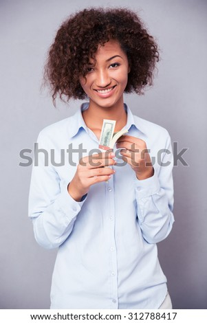 Portrait of a smiling afro american woman holding money on gray background - stock photo