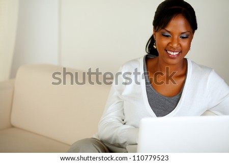 Portrait of a smiling afro-American woman using laptop while sitting on couch at home indoor - stock photo