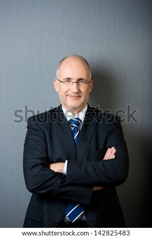 Portrait of a smiling and confident mature balding businessman, wearing a suit and a necktie, with arms crossed, in front of a gray wall - stock photo
