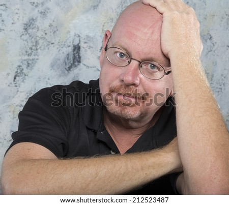Portrait of a smiling and confident mature balding senior man with arms  crossed, in front of a textured wall. - stock photo