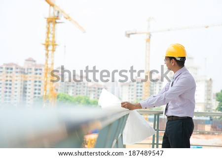 Portrait of a smiling Asian Indian male contractor engineer with hard hat inspecting at construction site. - stock photo