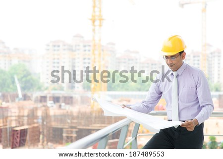 Portrait of a smiling Asian Indian male contractor engineer with hard hat reading blueprint at construction site. - stock photo