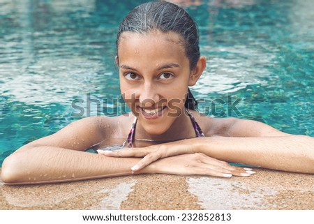 Portrait of a smiling attractive Asian woman with wet hair leaning on the tiled surround of a swimming pool in her bikini enjoying the hot summer sunshine - stock photo