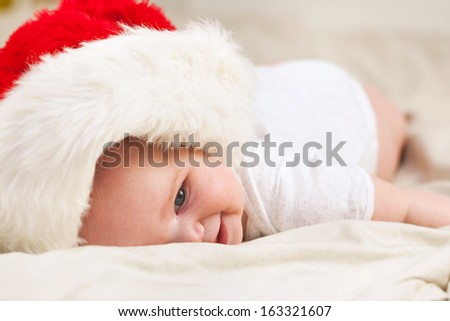 Portrait of a smiling baby girl on the bed in a cap of Santa Claus over white background - stock photo