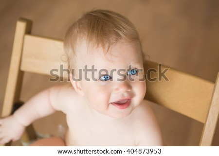 Portrait of a smiling baby on the chair in his room - stock photo