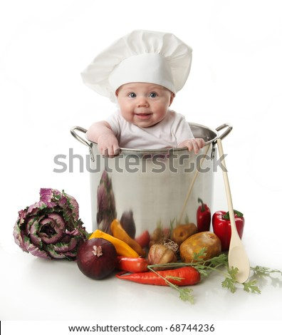 Portrait of a smiling baby sitting inside a large cooking stock pot surrounded by vegetables and food, isolated on white - stock photo
