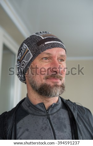 Portrait of a smiling bearded man, after jogging on a rainy day. - stock photo