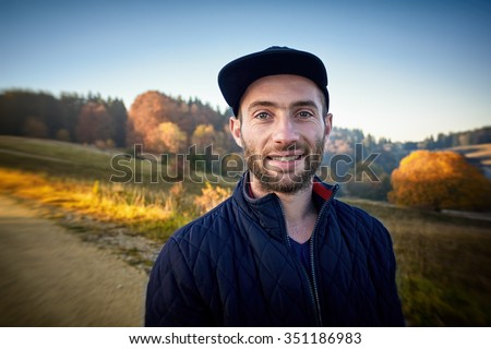 Portrait of a smiling bearded man in the woods. Fall season, blurred background. - stock photo