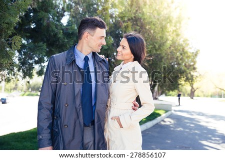 Portrait of a smiling beautiful couple dating in park - stock photo