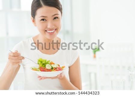 Portrait of a smiling beauty breakfasting with a vegetable salad - stock photo