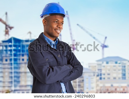 Portrait of a smiling black worker in front of a construction site - stock photo