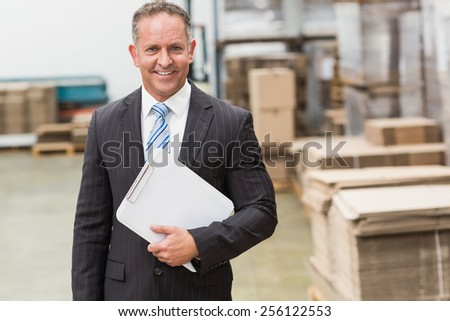 Portrait of a smiling boss holding clipboard in a large warehouse - stock photo