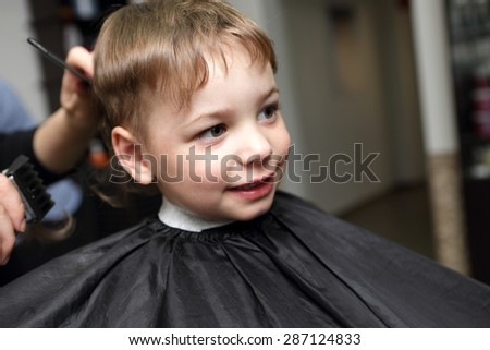 Portrait of a smiling boy at the barbershop - stock photo