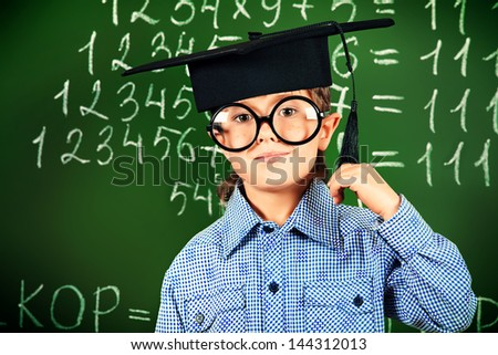 Portrait of a smiling boy in round glasses and academic hat standing near the blackboard in a classroom. - stock photo