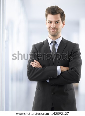 Portrait of a smiling business man standing in office with arms crossed. - stock photo