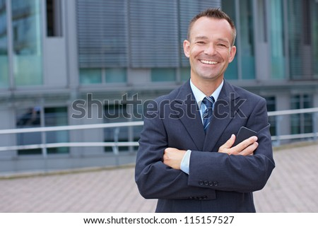 Portrait of a smiling business man with his arms crossed - stock photo