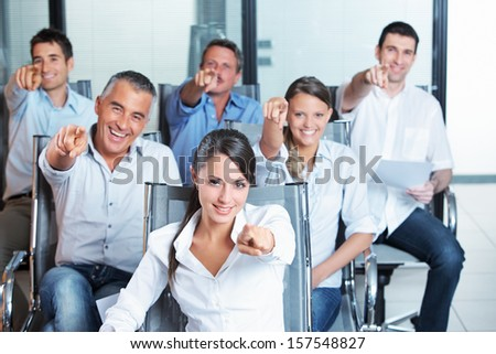 Portrait of a smiling business team pointing at you  - stock photo