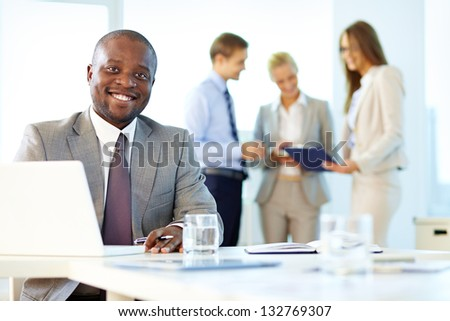 Portrait of a smiling businessman being at his workplace - stock photo