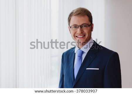 Portrait of a smiling businessman, dark blue suit with a blue tie and glasses, standing in office in front of windows. - stock photo