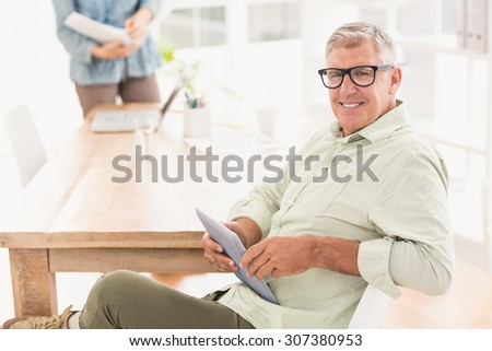 Portrait of a smiling businessman holding a tablet at office - stock photo