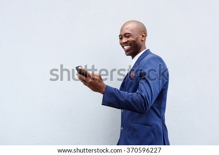 Portrait of a smiling businessman looking at cellphone  - stock photo