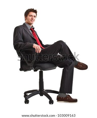 Portrait of a smiling businessman sitting on a chair - stock photo