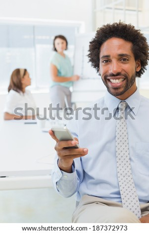 Portrait of a smiling businessman text messaging with colleagues in background at the office - stock photo