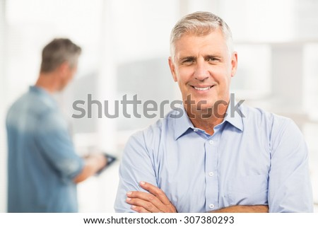 Portrait of a smiling businessman with arms folded at the office - stock photo