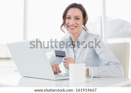 Portrait of a smiling businesswoman doing online shopping through laptop and credit card in office - stock photo