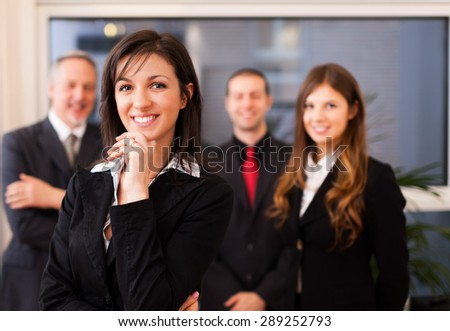 Portrait of a smiling businesswoman in front of her colleagues - stock photo