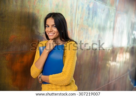 Portrait of a smiling businesswoman standing with folder in hallway and looking at camera - stock photo