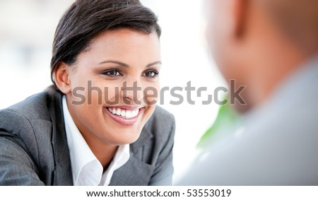 Portrait of a smiling businesswoman talking with her colleague in the office - stock photo