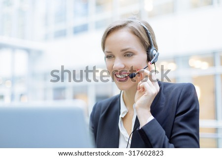 Portrait of a smiling Businesswoman using a head set - stock photo