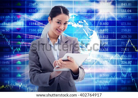 Portrait of a smiling businesswoman using a tablet computer against stocks and shares - stock photo