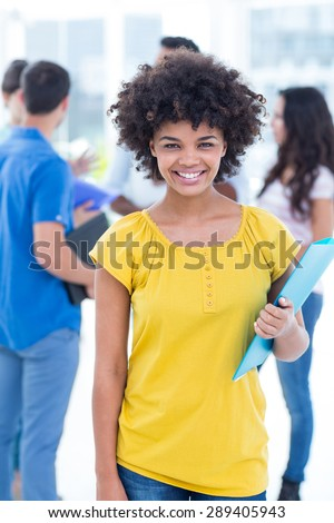 Portrait of a smiling businesswoman with his colleagues behind - stock photo