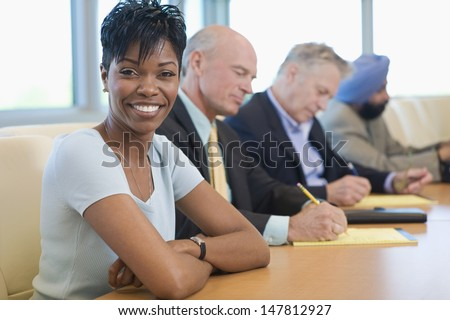 Portrait of a smiling businesswoman with multiethnic colleagues in conference room - stock photo
