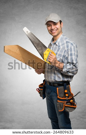 Portrait of a smiling carpenter holding wood planks. Gray grunge background - stock photo