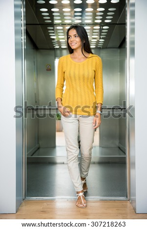 Portrait of a smiling casual businesswoman standing in elevator and looking away - stock photo