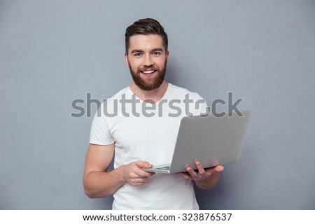 Portrait of a smiling casual man holding laptop over gray background - stock photo