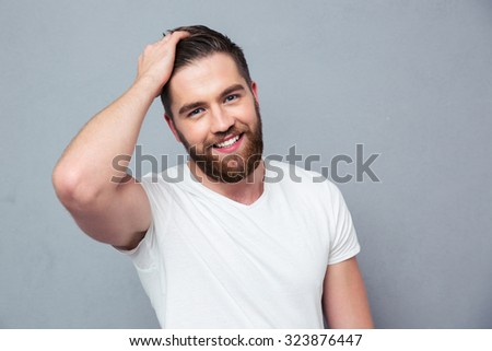 Portrait of a smiling casual man standing over gray background - stock photo