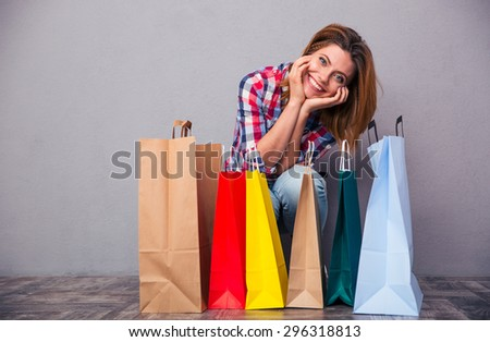 Portrait of a smiling casual woman sitting with shopping bags in studio. Looking at camera - stock photo