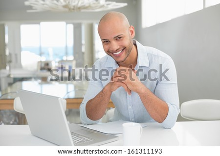 Portrait of a smiling casual young man using laptop at home - stock photo