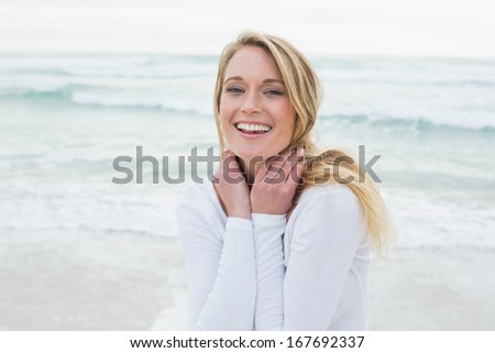 Portrait of a smiling casual young woman standing at the beach - stock photo