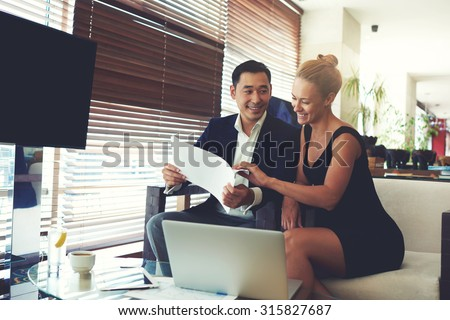 Portrait of a smiling cheerful business men and women watching together working papers while sitting with laptop computer in office space, young happy leadership received good results in their job - stock photo