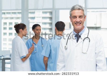 Portrait of a smiling confident male doctor at medical office - stock photo